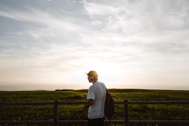 Homem encostado a uma cerca na floresta — Fotografia de Stock