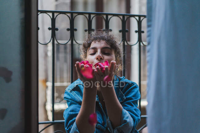 Pretty curly girl sitting in doorway and blowing rose petals away from hands having fun — Stock Photo