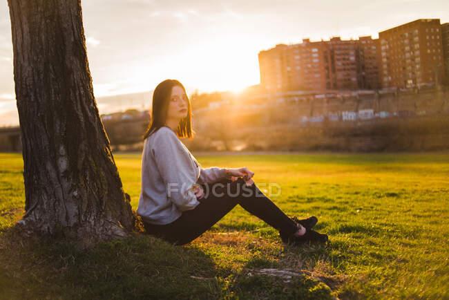 Woman under tree in sunlight — Stock Photo