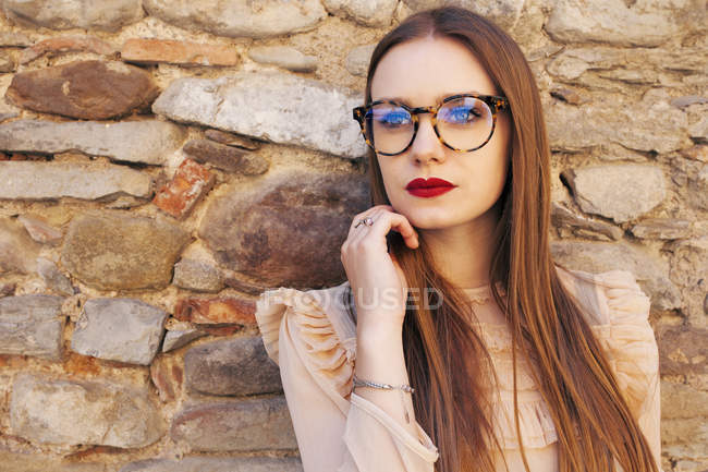 Young thoughtful woman in glasses standing against brick wall — Stock Photo
