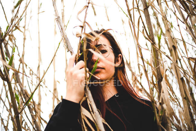 Mysterious girl wearing black outfit standing in tall dried grass and looking at camera — Stock Photo