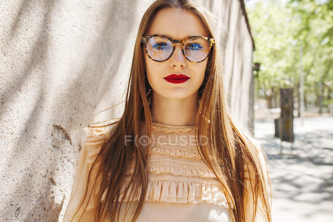 Young stylish woman in glasses standing next to stone wall on street — Stock Photo