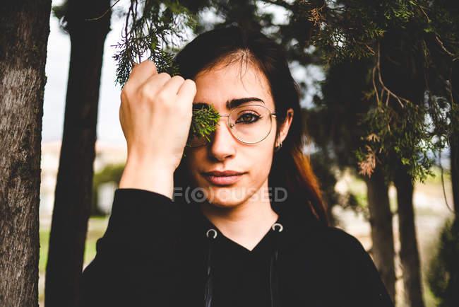 Mujer morena joven en los vidrios que cubren el ojo con una rama verde en bosque - foto de stock