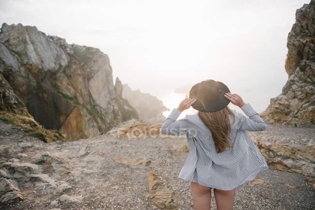 Mulher de camisa e chapéu em pé na costa rochosa e olhando para a vista — Fotografia de Stock