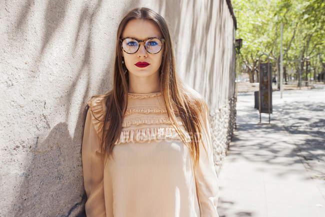 Молодая стильная женщина в очках опирается на каменную стену на улице — стоковое фото