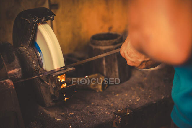 Crop smith using grindstone to sharpen metal blade in professional workshop — Stock Photo