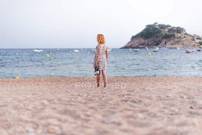 Vista laterale della donna delle colture che trasporta sandali mentre cammina sulla spiaggia sabbiosa all'oceano — Foto stock
