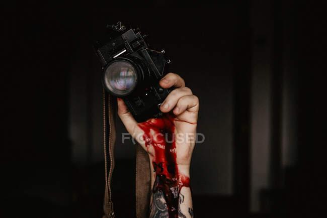 Кадр с татуированной рукой, держащей фотокамеру с густой темной кровью на черном фоне — стоковое фото