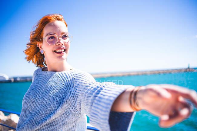 Joyeux rousse femme tirant la main et regardant loin tout en s'appuyant sur la main courante au bord de la mer. — Photo de stock