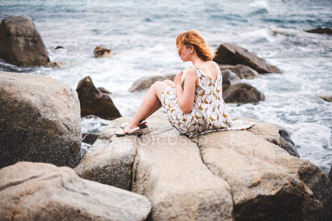 Side view of attractive woman holding hat and sitting on big stone at wavy ocean — Stock Photo