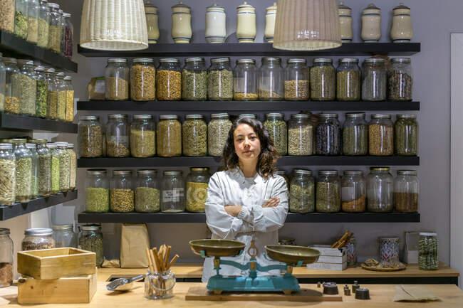 Жінка зі схрещеними руками в магазині прянощів. — стокове фото
