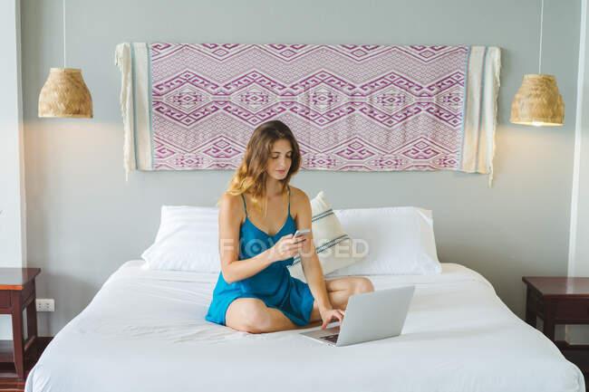 Mujer usando smartphone en la cama - foto de stock