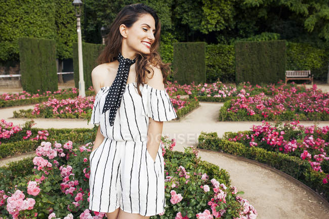 Happy elegant woman in striped summer jumpsuit standing in park with elegant with blooming pink flowers — Stock Photo