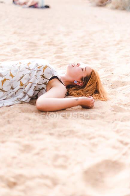 Вид сбоку на женщину, пинающую песок, лежа и расслабляясь на песчаном берегу — стоковое фото