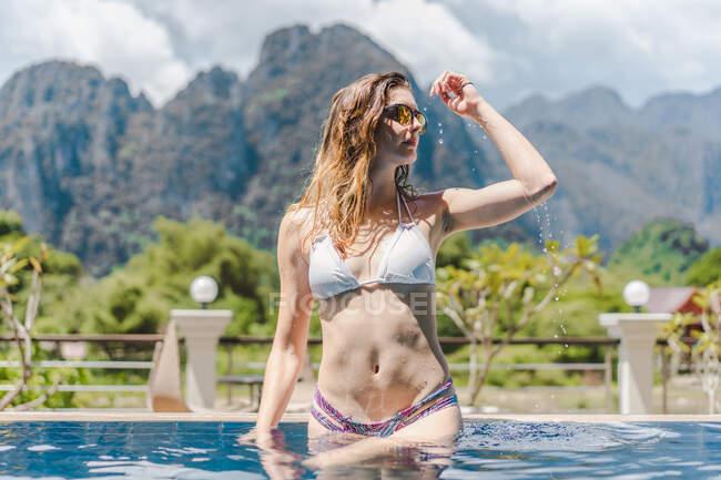 Seducente giovane donna in bikini in piedi in piscina sullo sfondo delle montagne. — Foto stock