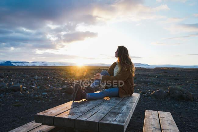 Persona seduta sul tavolo e che guarda in alto con lo smartphone — Foto stock