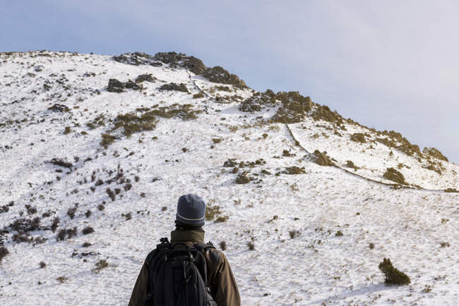 Young man with a backpack hiking enjoying in the snowy mountains on a winter sunny day. — Stock Photo