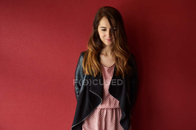 Young woman in jacket standing near red wall — Stock Photo