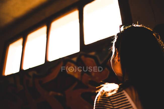 Mujer joven anónima dentro del edificio abandonado y mirando hacia arriba - foto de stock
