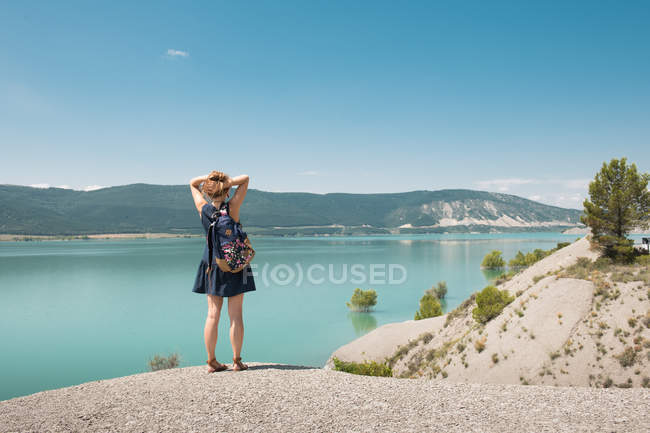 Woman with backpack standing at picturesque sea and looking at view — Stock Photo