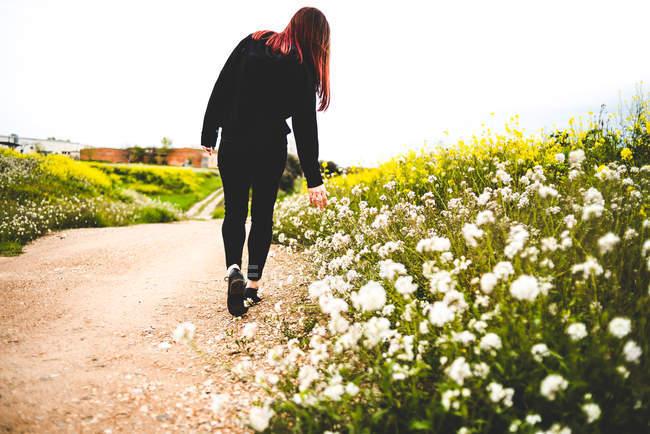 Menina em roupa preta em pé na estrada rural remota e tocando flores — Fotografia de Stock