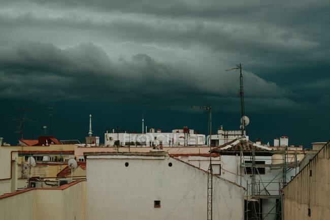 Techos de casas con antenas bajo el cielo oscuro con nubes de trueno - foto de stock