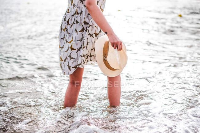 Vista posteriore di bella donna che tiene il cappello e in piedi in mare calmo sulla spiaggia nella baia — Foto stock