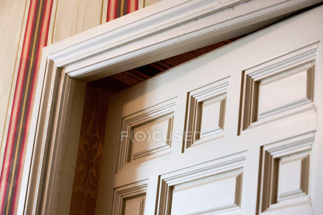 From below view of white ajar door corner in room with striped wallpaper — Stock Photo