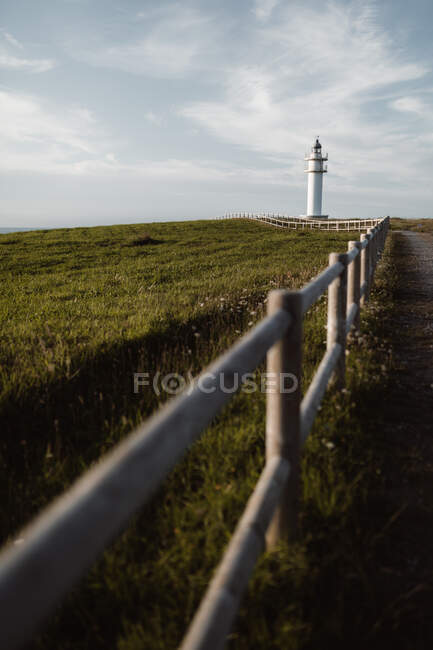 Fence and path on side and green field with white beacon and blue sky on the background in Cantabria, Spain — Stock Photo