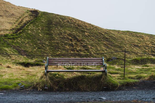Хорошая деревянная скамейка, стоящая на гравийной дороге в красивой исландской сельской местности в серый день — стоковое фото