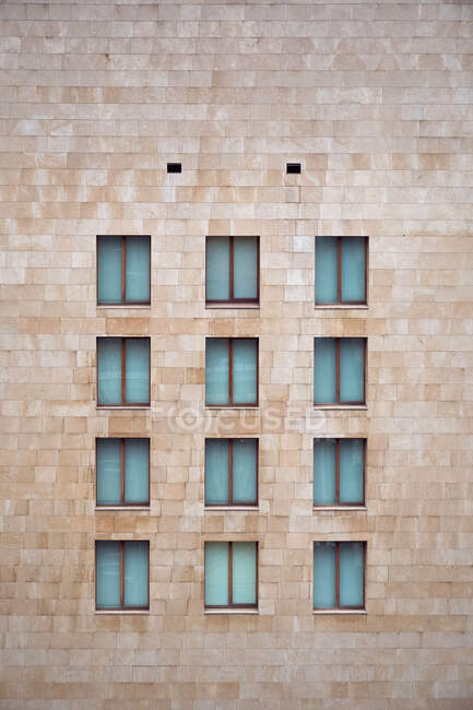 Light brown brick wall of building with little similar closed windows in Bilbao — Stock Photo