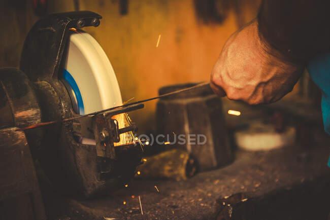 Коваль з допомогою шліфувального каменю для загострення металевого леза в професійній майстерні. — стокове фото