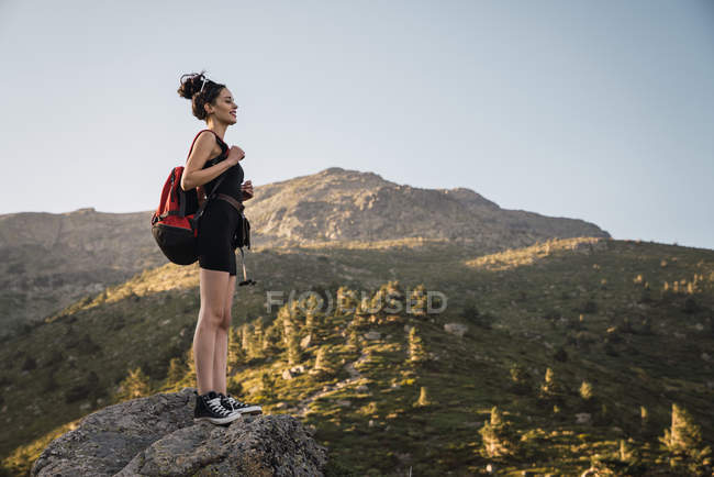 Young woman with backpack enjoying nature in mountains — Stock Photo