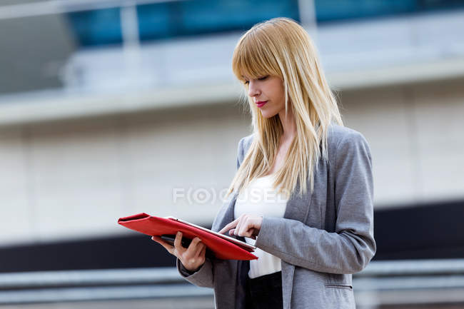 Blonde woman in suit standing on street and using tablet — Stock Photo