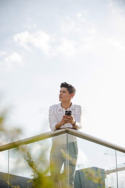 Giovane ragazzo in abito casual tenendo smartphone e guardando lontano mentre si appoggia su ringhiera su sfondo di cielo nuvoloso — Foto stock