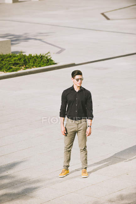 Confident man in black shirt and sunglasses standing on street — Stock Photo