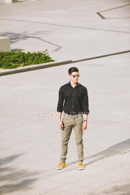 Впевнено людина в чорні сорочки і сонцезахисні окуляри, стоячи на вулиці — стокове фото