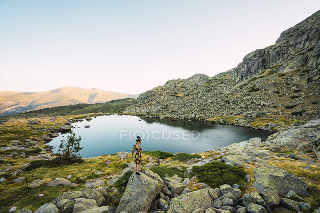 Scenic view at distance of woman standing on gray rocks on green shore of small calm lake in beautiful mountain range — Stock Photo