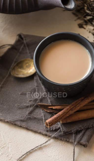 Tasse orientale de thé Chai au lait, cannelle, gingembre et cardamome sur toile grise — Photo de stock