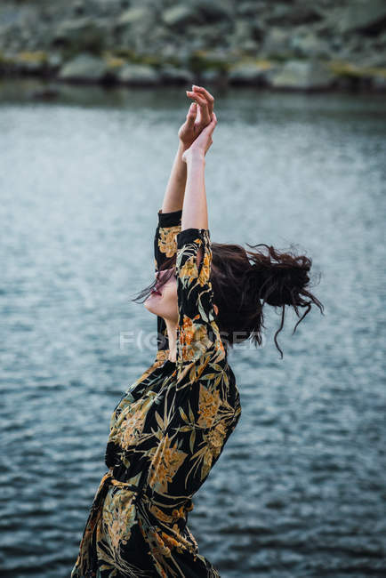 Young woman standing with outstretched arms alone on shore by lake water — Stock Photo
