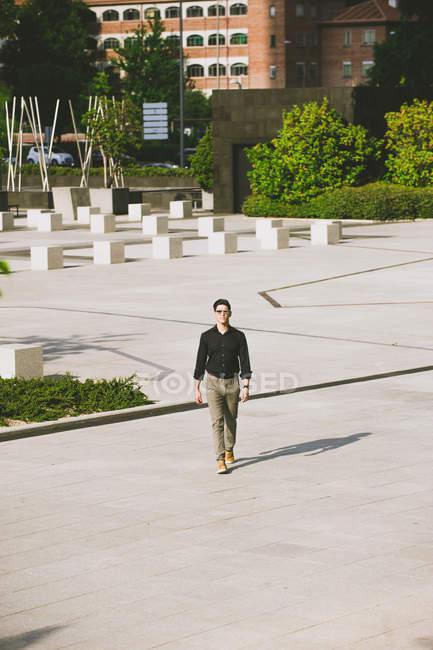 Homem confiante em óculos de sol e camisa preta andando na rua — Fotografia de Stock