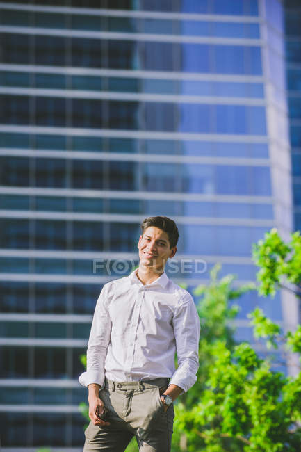 Positive young businessman standing against modern building and looking at camera — Stock Photo