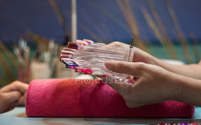 Frauenhände mit bunter Nagellackpalette im Schönheitssalon — Stockfoto