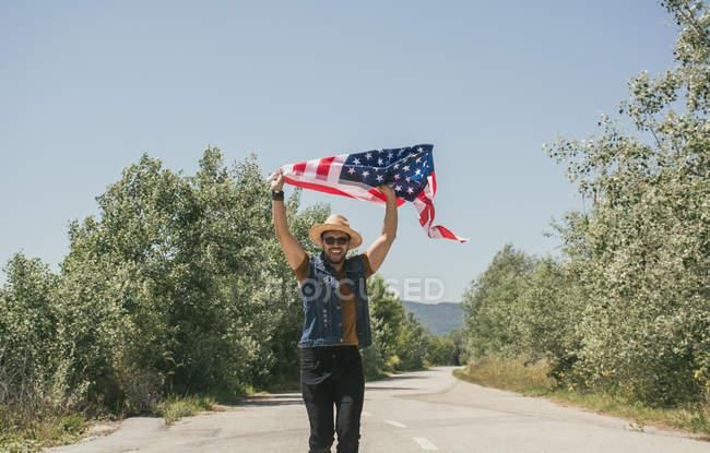 Homem de chapéu mostrando bandeira americana — Fotografia de Stock