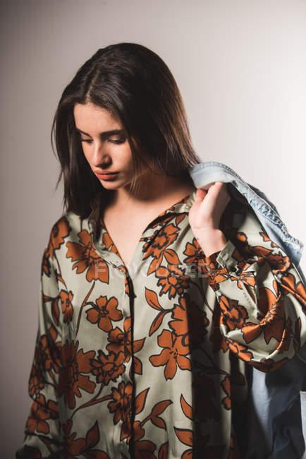 Ragazza in camicia fantasia in posa su sfondo grigio — Foto stock