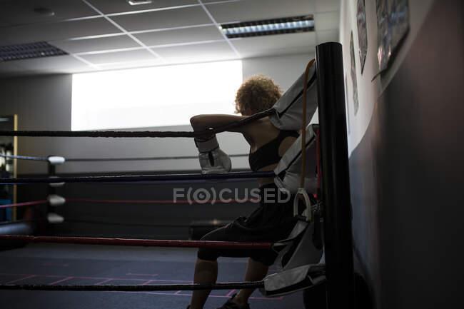 Erwachsene Dame in Boxhandschuhen stützt sich auf Ring — Stockfoto