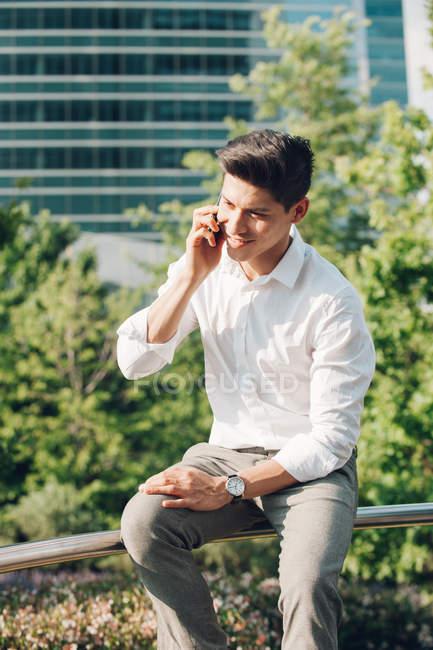 Joven hombre de negocios hablando por teléfono mientras está sentado en la barandilla al aire libre - foto de stock
