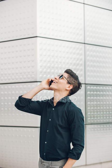 Alegre empresário falando no telefone contra a parede de construção — Fotografia de Stock