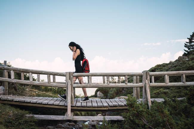 Vista laterale della donna casual con zaino rosso che cammina sul ponte pedonale in legno nella valle verde contro il cielo blu — Foto stock