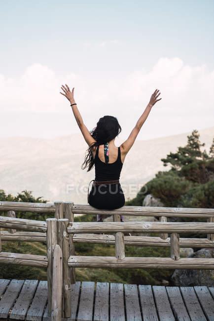 Mulher magro sentado na cerca acima do vale, vista traseira — Fotografia de Stock